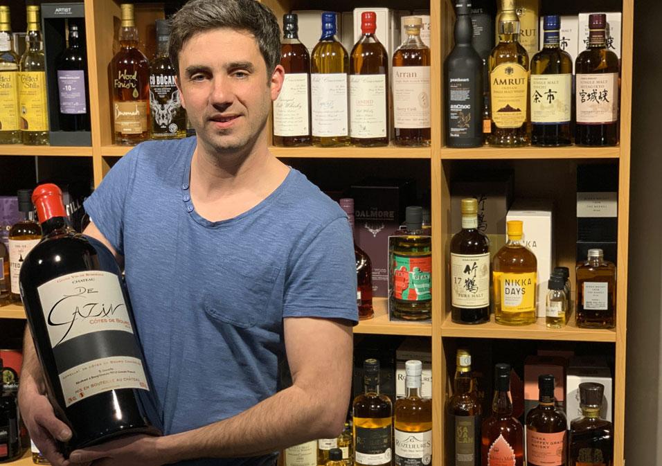 Votre caviste Julien porte une bouteille de vin rouge