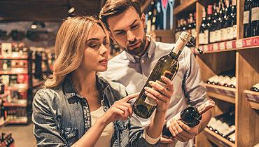 deux personnes choisissent une bouteille de vin dans une cave