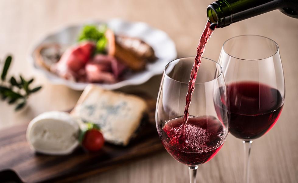 une personne sert un verre de vin